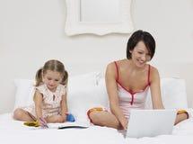 Moder- och dotterteckning och användabärbar dator royaltyfri bild