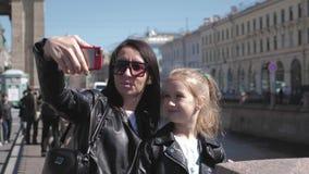 Moder- och dottertonåring som tar selfieståenden på smartphonen i stad Familj-, lopp- och turismbegrepp stock video