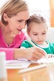Moder- och dotterwriting tillsammans Arkivfoto