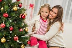 Moder och Dughter som dekorerar julgranen Arkivfoto