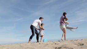 Moder och fader Spinning Their Son och dotter på stranden stock video
