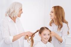Moder- och farmordanandehår av flickan i en fläta Arkivfoton