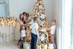 Moder och fem barn som dekorerar en julgran royaltyfria foton