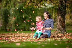 Moder och flicka som har gyckel under träd med höstsidor i parkera, den blonda gulliga lockiga lycklig och ung familjen för flick arkivfoto