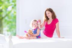 Moder och gullig dotter som borstar hår royaltyfria foton