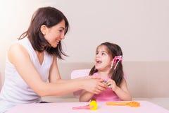 Moder och gullig flicka som spelar samman med playdough arkivfoto