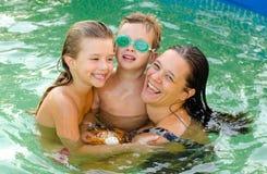 Moder och hennes barn i simbassängen Royaltyfria Bilder