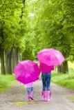 Moder och hennes dotter med paraplyer Arkivbild