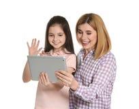 Moder och hennes dotter som använder video pratstund på minnestavlan arkivbilder
