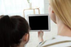 Moder och hennes dotter som hemma använder video pratstund på minnestavlan royaltyfri foto