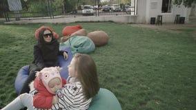 Moder och hennes lilla döttrar i utomhus Lilla flickan går till hennes syster som kramar och kysser henne lager videofilmer