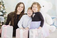 Moder och hennes tv? lilla barn med julg?vaaskar Familj p? julhelgdagsafton Moder och sm? ungar som ?ppnar Xmas arkivfoton