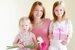 Moder och honom döttrar som ger en gåva Arkivbilder