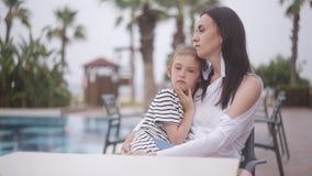 Moder och ledset dottersammanträde på en tabell vid pölen stock video