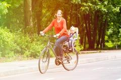 Moder och liten dotter på cykeln i sommar royaltyfri foto