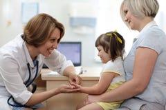 Moder och liten dotter som besöker det pediatriskt Konsulterande kvinna för doktor med barnet arkivbild
