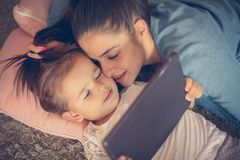 Moder och liten dotter som hemma tycker om och använder pik fotografering för bildbyråer