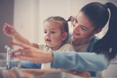 Moder och liten dotter som spelar och bakar kakor i K fotografering för bildbyråer