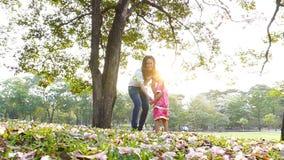 Moder och liten dotter som tillsammans spelar i en parkera stock video