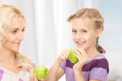 Moder och liten flicka med det gröna äpplet Royaltyfri Foto