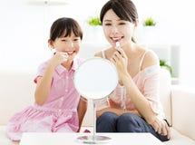 Moder och liten flicka som gör din makeup Royaltyfria Bilder