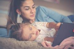 Moder och liten flicka som hemma tycker om och använder iPod Cl fotografering för bildbyråer
