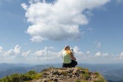 Moder- och liten flickaanseende på en klippa överst av berget som ner ser Royaltyfri Bild