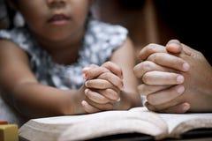 Moder- och liten flickahänder vek i bön på en helig bibel Royaltyfri Fotografi