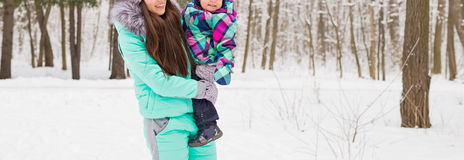 Moder och liten litet barnflicka som går i vinterskogen och har gyckel med snö tycka om familjvinter Jul royaltyfri bild