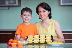Moder och liten son som framlägger deras muffin Arkivbild