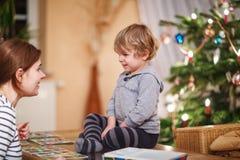 Moder och liten son som tillsammans spelar utbildningskortspelet för c Arkivbild