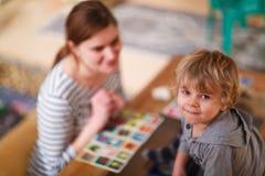 Moder och liten son som tillsammans spelar utbildningskortspelet för c Royaltyfri Bild