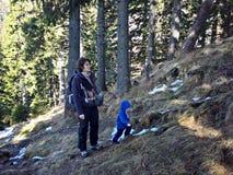 Moder och litet barn som trekking i bergen Arkivfoto
