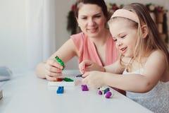 Moder- och litet barndotter som hemma spelar med plasticine eller lekdeg Royaltyfria Foton