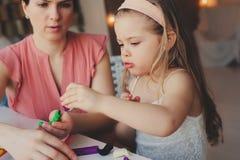 Moder- och litet barndotter som hemma spelar med plasticine eller lekdeg Arkivbild