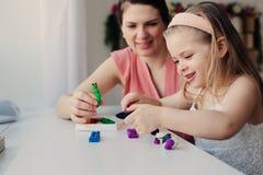Moder- och litet barndotter som hemma spelar med plasticine eller lekdeg Arkivfoton