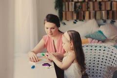 Moder- och litet barndotter som hemma spelar med plasticine eller lekdeg Arkivfoto