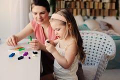 Moder- och litet barndotter som hemma spelar med plasticine eller lekdeg Royaltyfri Bild