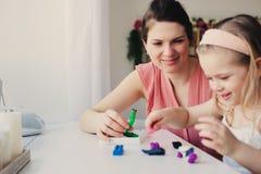 Moder- och litet barndotter som hemma spelar med plasticine eller lekdeg Arkivbilder