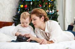 Moder- och litet barnson som spelar med RC-kontrollanten Arkivbild
