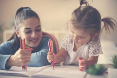 Moder och lycklig flicka som tillsammans spelar och hemma skriver arkivfoton