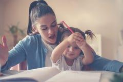 Moder och lycklig flicka som tillsammans spelar och skriver på hom royaltyfri fotografi