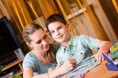 Moder och pojke som gör läxa som metas tillsammans Arkivbild