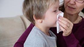 Moder och pys med den körande näsan, mamma som tar omsorg av hennes sjuka litet barnpojke lager videofilmer