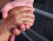 Moder- och solinnehavhänder stänger sig upp Arkivfoton