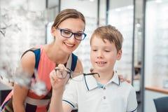 Moder och son båda böjelse som glasögon som erbjuds i optiker, shoppar royaltyfria bilder