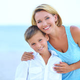Moder och son i omfamning på stranden Royaltyfria Foton