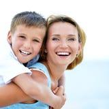 Moder och son i omfamning på stranden Fotografering för Bildbyråer