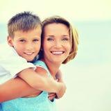 Moder och son i omfamning på stranden Royaltyfria Bilder