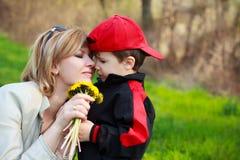 Moder och son med blommor royaltyfri bild